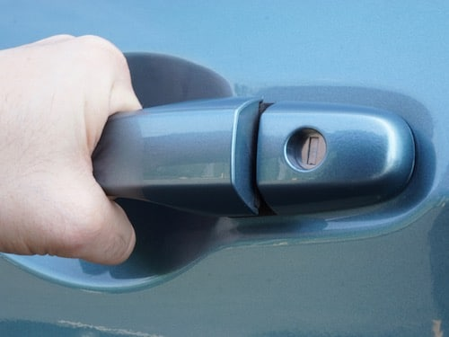 hand pulling on car door handle