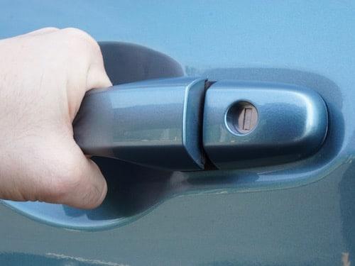 hand pulling on car door handle